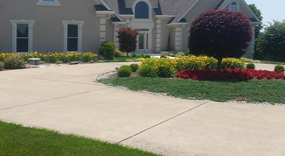 interested in designing or building a landscape like this tree surrounded by flowers in a circular driveway, check out Careers at Walnut Ridge Landscaping