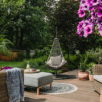 patio design with hammock chair and outdoor funiture looking into wooded area