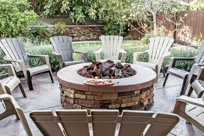 patio designs should include seating like this circle of chairs around a fireplace