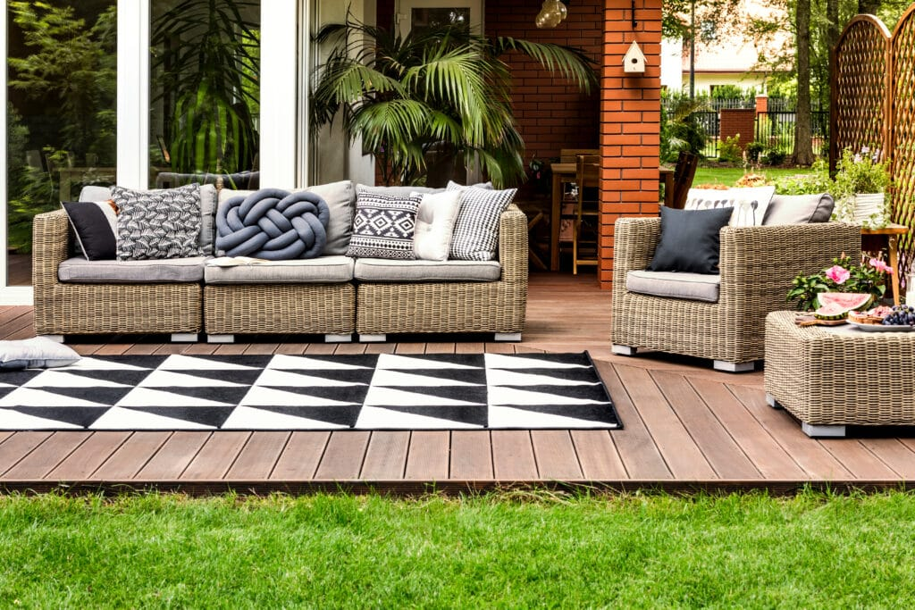 patio design with wicker furniture, stained decking and a black and white carpet